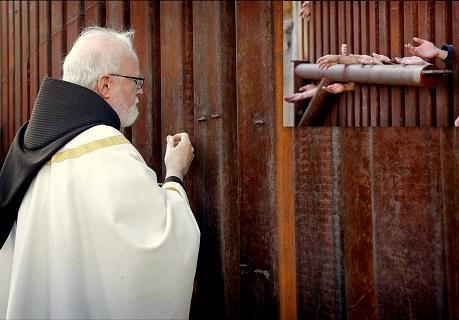 L'arcivescovo di Boston O'Malley dà la comunione a migranti dall'altra parte del muro di frontiera