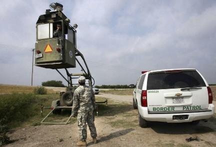 Un membro della Guardia Nazionale osserva un suo collega della Pattuglia di Frontiera in un Skybox (Foto AP)