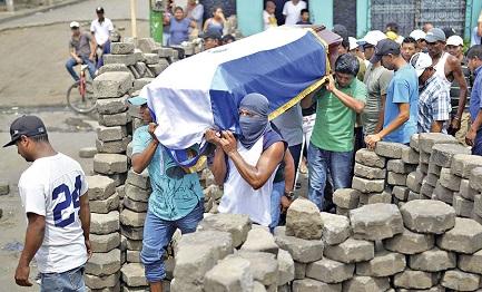 Una barricata a Masaya, con manifestanti che portano la bara di un caduto sulle spalle