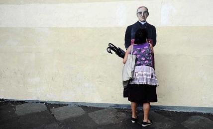 Una donna bacia un murales con Romero dipinto su una parete di San Salvador